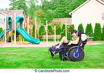 Smiling disabled boy in wheelchair sitting at a park
