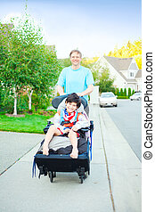Father pushing ten year old  disabled son in wheelchair outdoors