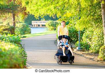 Father walking with disabled son in wheelchair at park