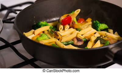 Primavera Pasta with mushrooms cooking in a pan