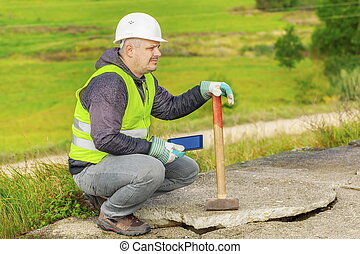 Worker with sledgehammer and tablet PC near broken concrete...