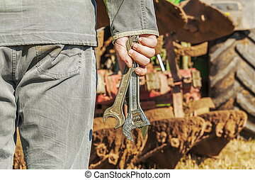 Worker with wrenches near the tractor