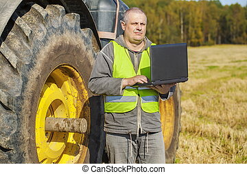 Farmer with computer near the tractor on field