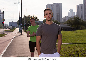 Two young men jogging through the city - athletic young men...