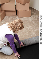 Moving in - Attractive Caucasian woman rolling out a new...