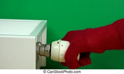 hand with glove adjusting home temperature with radiator thermostat handle.