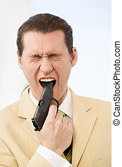 Shooting - Portrait of scared young businessman putting gun...