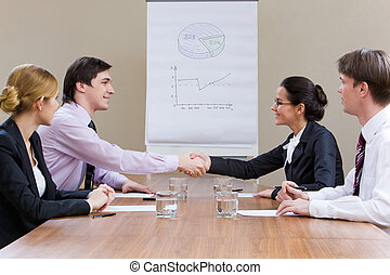 Agreement - Photo of smiling business partners handshaking...