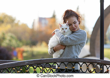 young lady with Maine Coon cat on the bridge