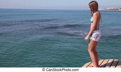 Jump off the pier - Teenager girl jumping from pier into the...