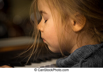 little girl playing on the keys of the piano, closeup