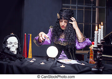Sorceress while practising witchcraft - Sorceress looking at...