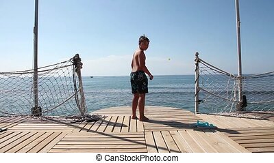 Jump off the sea pier - Teenager boy is jumping into the sea...