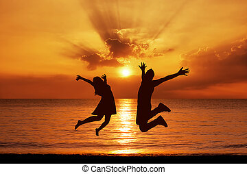 Silhouettes of happy couple jumping on background of sea at...