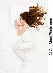 Resting - Above view of sleeping woman under white satin...