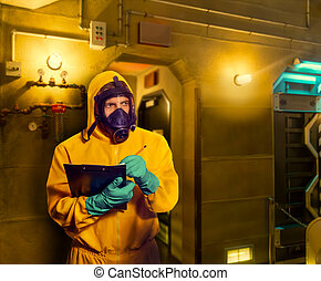 Man in protective suit with respiratory mask making notes