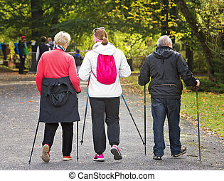 Three people in the park - Nordic walking