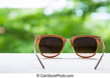 glasses on table with nature background in summer