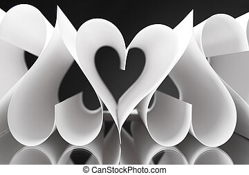 Hearts - Paper heart shapes next to each other over black...
