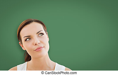 Attractive Young Woman Looking Up to Blank Chalk Board