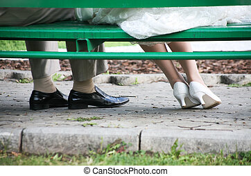 Solitude - Close-up of legs of newly weds under bench in the...