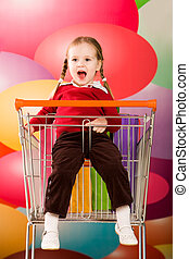 Naughty kid - Portrait of surprised girl sitting in handcart...