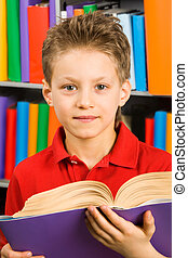 Reader - Portrait of smart boy with open book looking at...