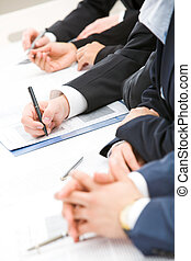 Paper work - Image of row of people hands over papers during...
