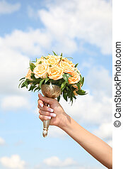 Bridal bouquet - Close-up of bridal hand holding yellow rose...