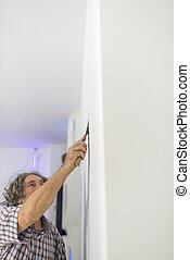 Decorator retouching imperfections in a wall