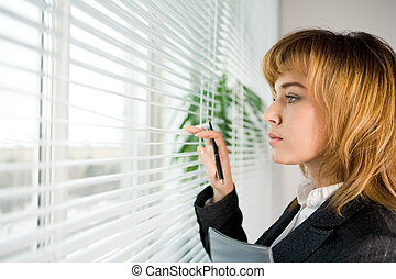 Looking through blinds - Profile of confident female looking...