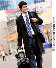 Traveller - Image of happy guy in suit and coat walking with...