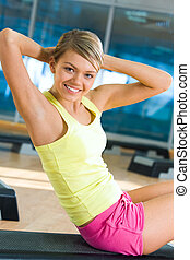 Sit-ups - Portrait of healthy woman doing sit-ups looking at...