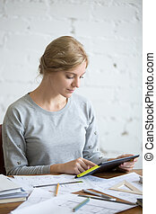 Portrait of an attractive woman working with a tablet...