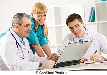 Physicians at work - Group of therapists looking at laptop...
