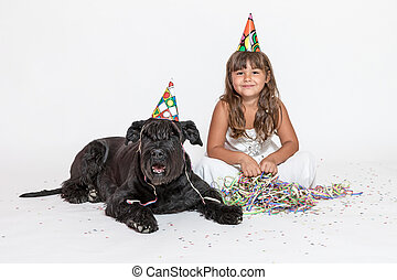 Cute little girl with lying black dog on the white - Cute...