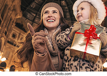 mother and daughter with Christmas gift pointing on...