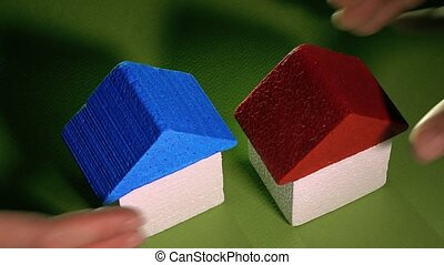 Man and woman taking away toy houses against green...