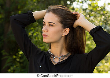 Young woman fixing her hair - Good-looking young woman in...