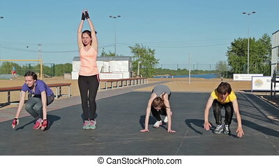 Girls doing burpee exercise, and another exercise, outdoor...