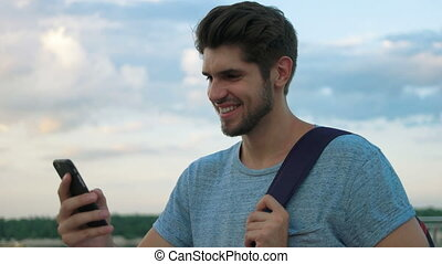 Smiling man using his phone.