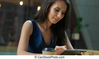 Working at the cafe. Young beautiful long hair woman sitting at the table and using tablet computer in outdoor cafe