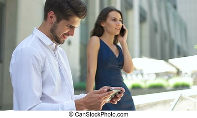 Young lady talking on her phone , while her colleague use his tablet.