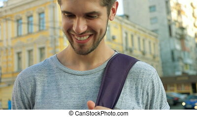 Young handsome man using his phone in city