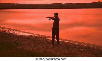 man is engaged in gymnastics yoga on the nature of the sunset silhouette sport red