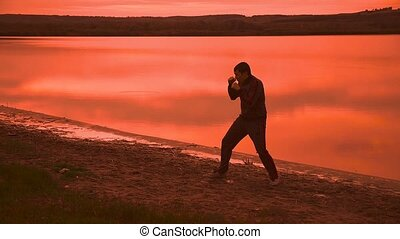 man engaged in melee combat sports boxing at sunset shadow...