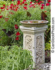 Bird Bath in a garden with red flowers
