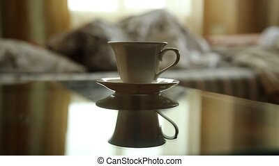 closeup cup of hot tea or coffee, young sexy woman waking up...