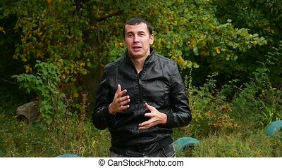 man in a leather jacket Autumn talking hand gestures...