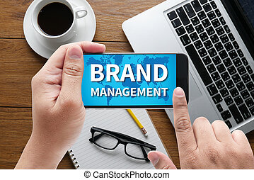 BRAND MANAGEMENT message on hand holding to touch a phone,...